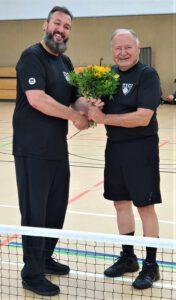 Coach Dale übergibt Wolfgang ein paar Blumen